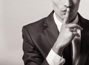 איש עם אצבע על הפה שמסמל שתיקה