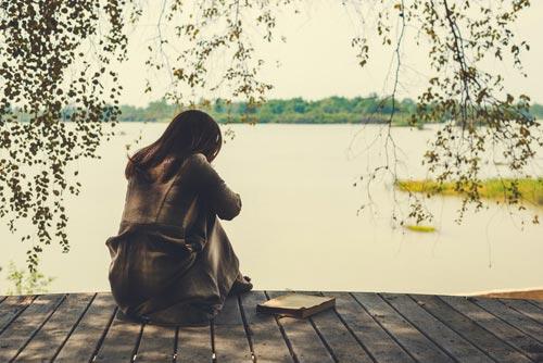 אישה יושבת בעצבות