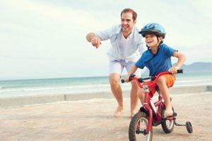 אב מוביל את בנו באופניים