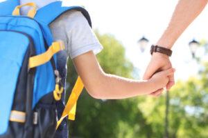 ילד עם ילקוט נותן יד למבוגר